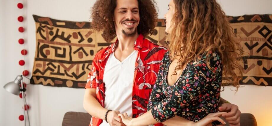 Una pareja sonriente bailando bachata en casa