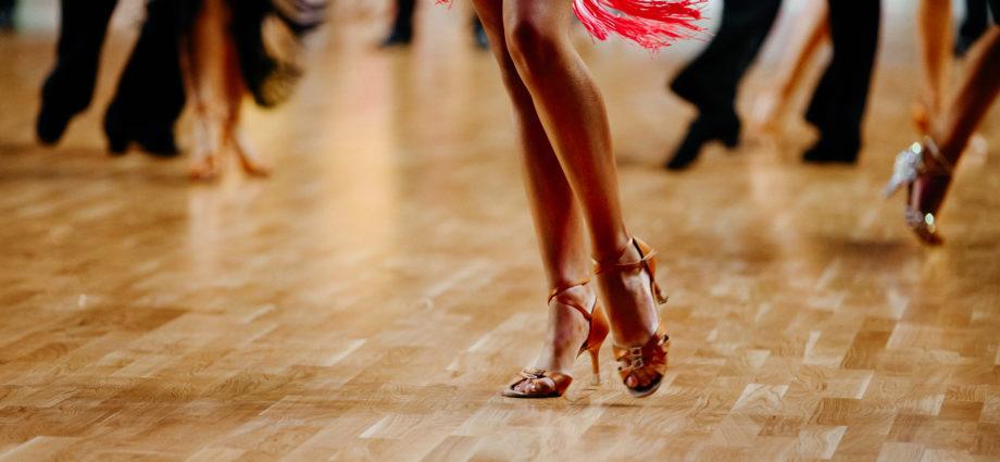 Female Latin dancer dancing alone on crowded floor