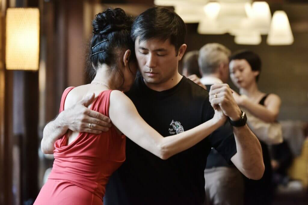 Couple in Argentine tango hold in dance class