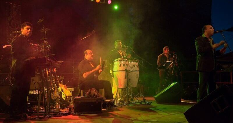 Live salsa band plays clave, congas, piano