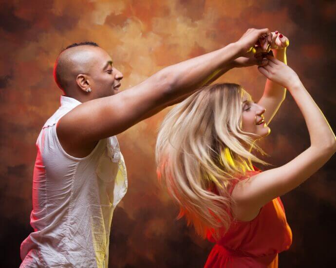 Smiling couple dance salsa