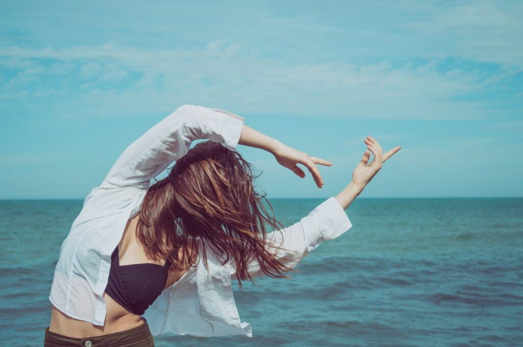 A woman dances alone in front of the ocean