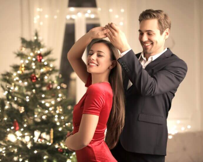 Latin dancers in front of Christmas tree and gifts