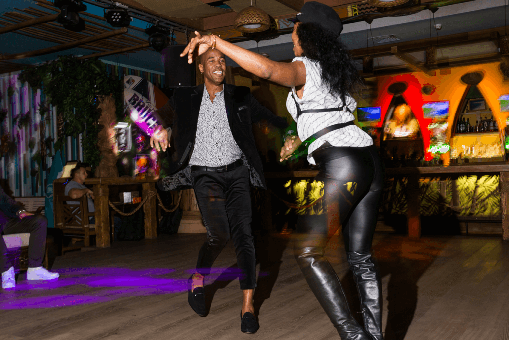 A woman does arm styling while dancing salsa with her partner
