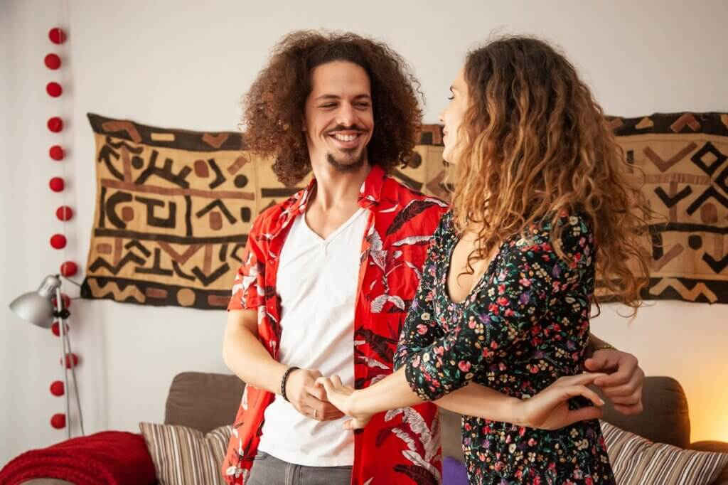 Smiling couple are dancing bachata at home during lockdown