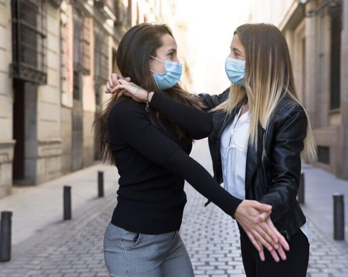 Two women dance bachata while wearing medical masks