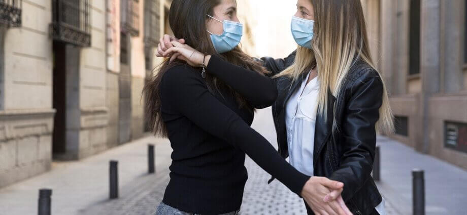Two women dance bachata while wearing medical masks