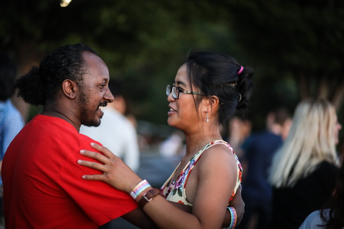 Follow suggests moves while dancing with a smiling partner in outdoor party