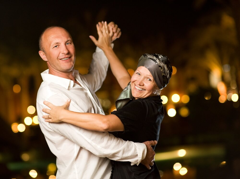 Middle-aged couple smile while dancing the waltz outside