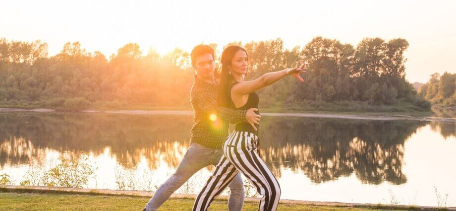 Follow does arm styling while dancing bachata with partner
