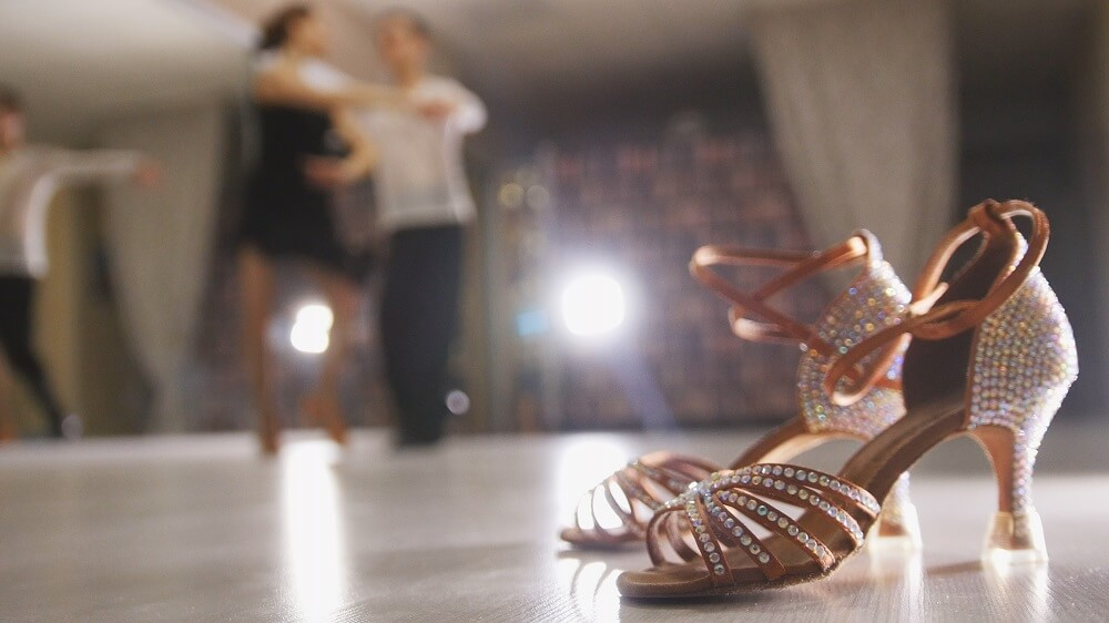 Stiletto salsa dance shoes in the corner of a dance floor