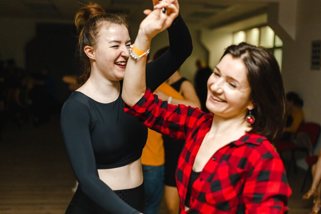 Two women dance salsa romántica together