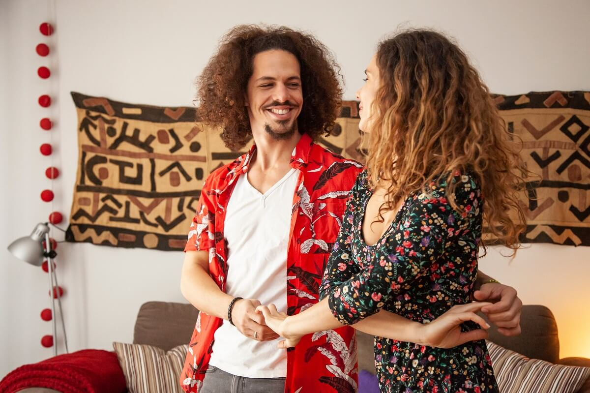 Smiling leader and follower dance bachata at home