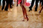 Female Latin dancer dancing alone on crowded floor